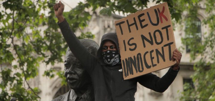 """A woman holds up a cardboard sign that says """"The UK is not innocent"""" with her fist in the air. From a protest in London."""