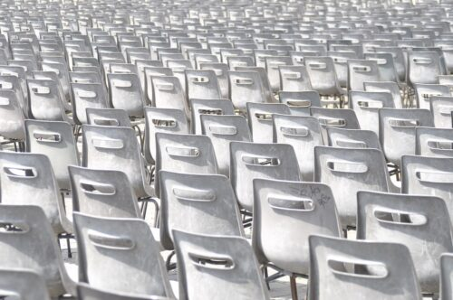 The frame is full of rows of white chairs, seen from behind.
